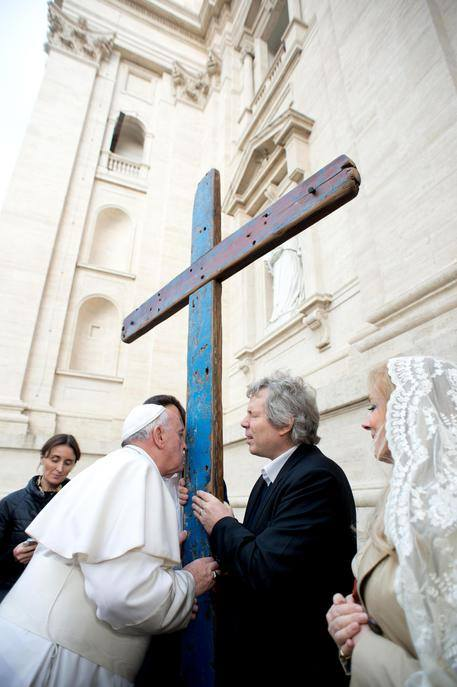 Bergoglio kisses the cross which is made with wooden barges. Islamic migrants to Lampedusa