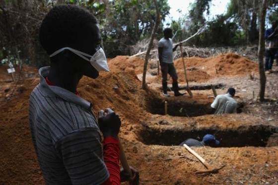 Grave diggers prepare for new Ebola victim outside an Ebola treatment center in Gbarnga, Liberia