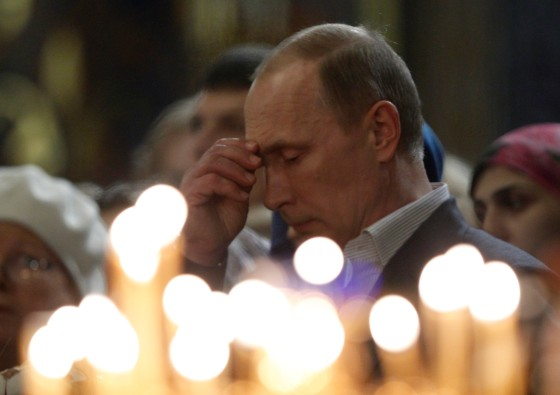 Vladimir Putin crosses himself as he attends the Orthodox Christmas service at the Holy Face of Christ the Savior Church in Sochi, Jan. 6, 2014.