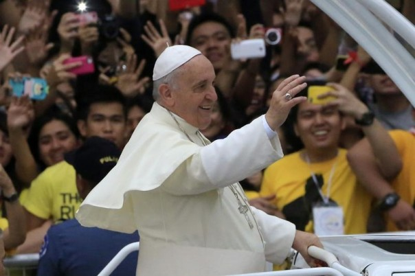 Pope Francis waves to pilgrims as he passes by with his motorcade during a meeting with youths at the University of Santo Tomas (UST) in Manila, Philippines, January 18, 2015. REUTERS/Romeo Ranoc