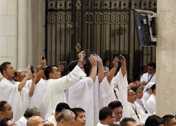 Filipino priests use their smart phones to take pictures of Pope Francis on a monitor during a mass for clergy and religious at the Cathedral Basilica of the Immaculate Conception in Manila on Jan. 16.