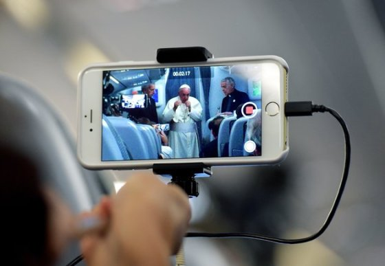 A journalist takes with his mobile phone a picture of Pope Francis during a press conference on July 13, 2015, onboard a plane on his way back to Rome from Paraguay, the final stop of his South America tour. Pope Francis departed Paraguay , bringing to a close a weeklong visit where he drew attention to the poor and marginalized in some of the region's poorest nations.      AFP PHOTO / VINCENZO PINTO        (Photo credit should read VINCENZO PINTO/AFP/Getty Images)