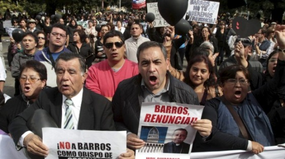 Politician Fidel Espinoza, right, and fellow Chileans protest as Bishop Juan Barros conducts his first service as bishop in Osorno cathedral, south of Santiago. Photo - Reuters